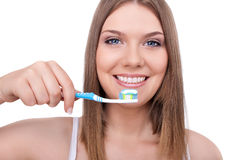 Healthy teeth. Young woman smiling with healthy teeth and a tooth-brush, isolated on white Stock Photos