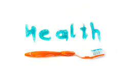 Healthy teeth concept. Health written with blue toothpaste gel. Underlined with a toothbrush Stock Photography