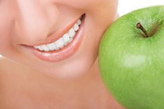 Healthy teeth and green apple. Smiling woman mouth with great white teeth. Close up. Beauty and dental health. Pretty woman. Smiling, whitening concept stock image