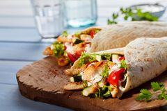 Healthy Tex-Mex tortilla wraps. Two Healthy Tex-Mex tortilla wraps viewed from side on wooden cutting board, glasses in background royalty free stock photo