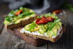 Healthy toast with avocado, goats cheese and arugula Royalty Free Stock Photo