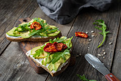 Healthy toast with avocado, goats cheese and arugula Stock Photos