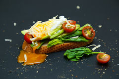 Healthy toast with avocado, tomatoes, spinach and poached egg. Stock Photo