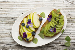 Healthy toast with green apple and juicy Kiwi with edible flowers of garden violas on a marble background. Color year. Greenery. Top Royalty Free Stock Image