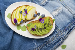 Healthy toast with green apple and juicy Kiwi with edible flowers of garden violas on a marble background. Color year. Greenery. Top Stock Image