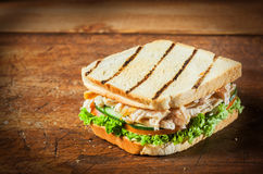Healthy toasted chicken breast sandwich. With shredded meat on fresh salad ingredients including lettuce, tomato and cucumber, on a rustic wooden table with stock images