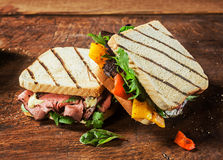 Healthy toasted sandwiches from a BBQ picnic. Healthy toasted and grilled sandwiches from a BBQ picnic with rare roast beef, cheese, pepper, rocket and spinach royalty free stock images