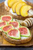 Healthy toasts or sandwiches with cream cheese, ripe figs and peaches drizzled with honey. Wooden dipper. Top view, close up Stock Images
