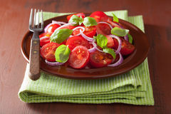 Healthy tomato salad with onion basil olive oil and balsamic vin Stock Photography