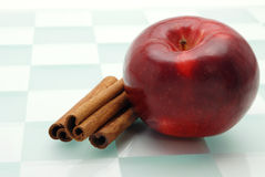 Healthy Treat. Shiny red apple and cinnamon sticks isolated on a checked background Royalty Free Stock Image