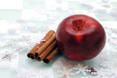Healthy Treat. Shiny red apple and cinnamon sticks isolated on a checked background with snowflakes Stock Photo