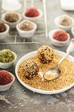 Healthy truffles with dates and nuts. Covered in sesame seeds, strawberry and matcha powder stock image