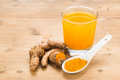 Healthy turmeric roots drinks in a transparent glass on wooden s Royalty Free Stock Photo