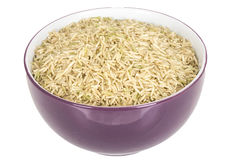 Healthy Uncooked Raw Brown Rice Served in Purple Dish Royalty Free Stock Photography