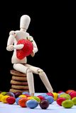 Healthy and unhealthy food. Wooden mannequin, holding a strawberry, surrounded by candy stock photo