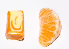Healthy and unhealthy food. Segment of mandarine and fruit toffee on the white background Royalty Free Stock Images