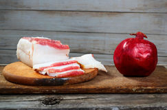 Healthy and unhealthy food. Fatty bacon and pomegranate on woode Stock Image