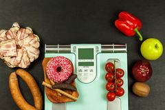 Healthy and unhealthy food. Obesity concept. Modern digital weight and bacon. Weight control on diet.  royalty free stock image