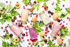 Healthy and useful colorful berry cokctalis, smoothies and milks. Hakes with yogurt, fresh fruit and berries on gray table, top view royalty free stock image