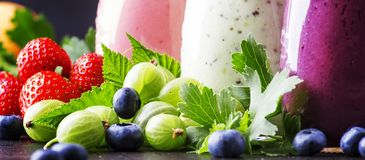 Healthy and useful colorful berry cokctalis, smoothies and milks. Hakes with yogurt, fresh fruit and berries on brown table, selective focus stock image
