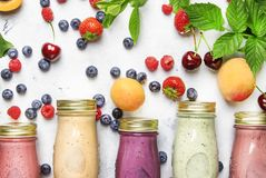 Healthy and useful colorful berry cokctalis, smoothies and milkshakes with yogurt, fresh fruit and berries on gray table, top view stock images