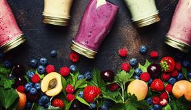 Healthy and useful colorful berry smoothies with yogurt, fresh f. Ruit and raw berries on brown background, top view royalty free stock photos