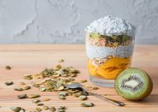 Healthy vanilla pudding of a chia in a glass with granola, mango and a kiwi royalty free stock photos