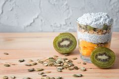 Healthy vanilla pudding of a chia in a glass with granola, mango and a kiwi stock photo