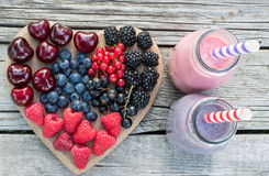 Healthy various fruits on heart and smoothies. Diet abstract concept . Healthy various fruits on heart and smoothies on vintage wooden background. Diet abstract stock photography