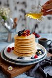 Woman`s hand is putting honey on breakfast homemade pancakes with forest berries. stock image