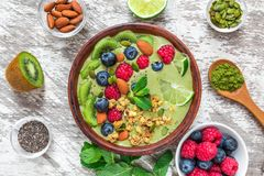 Healthy vegan breakfast. matcha green tea smoothie bowl with fresh fruits, berries, nuts, seeds and granola. top view