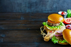 Healthy vegan burger. Healthy veggie burger with quinoa patty, lettuce and tomatoes, served on little wooden board over dark wooden background, selective focus Royalty Free Stock Images
