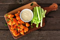 Free Healthy Vegan Cauliflower Buffalo Wings With Celery And Ranch Dip, Top View On A Wood Paddle Board Royalty Free Stock Images - 156851319