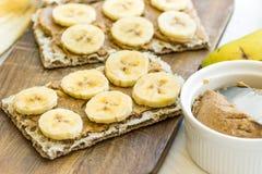 Healthy vegan dessert homemade peanut butter and banana sandwich with Swedish whole grain crispbread, breakfast, kitchen table Stock Image