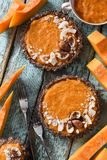 Healthy vegan dessert. Homemade tarts with nuts and oatmeal crus. T and pumpking filling served with raw pumpkin on blue background above view royalty free stock photos