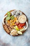 Healthy vegan dessert snacks - protein granola bars, homemade raw energy balls, cashew butter, toasted coconut chips. Cape gooseberry, kiwi, blood orange royalty free stock photo