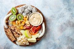 Healthy vegan dessert snacks - protein granola bars, homemade raw energy balls, cashew butter, toasted coconut chips. Cape gooseberry, kiwi, blood orange stock image