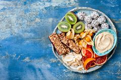 Healthy vegan dessert snacks - protein granola bars, homemade raw energy balls, cashew butter, toasted coconut chips. Cape gooseberry, kiwi, blood orange royalty free stock photography