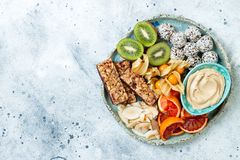 Healthy vegan dessert snacks - protein granola bars, homemade raw energy balls, cashew butter, toasted coconut chips. Cape gooseberry, kiwi, blood orange royalty free stock images