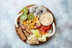 Healthy vegan dessert snacks - protein granola bars, homemade raw energy balls, cashew butter, toasted coconut chips. Cape gooseberry, kiwi, blood orange royalty free stock image