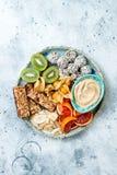 Healthy vegan dessert snacks - protein granola bars, homemade raw energy balls, cashew butter, toasted coconut chips. Cape gooseberry, kiwi, blood orange stock photography