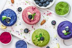Healthy vegan desserts. assortment of raw cashew cakes with matcha, acai, blueberry, mint and nuts. gluten free diet stock image