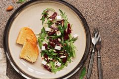 Healthy vegan diet salad with beetroot, arugula, feta cheese, nuts and seeds over brown stone background. Top view, flat lay stock photos