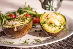 Healthy vegan dishes - avocado baked with egg. And rucola salad with tomatoes stock photo