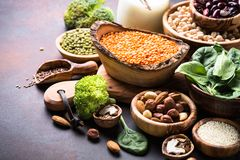 Healthy vegan food assortment. Leguminous, nuts, broccoli, spinach  and seeds on dark rusty table with copy space Stock Image