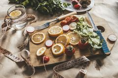 Healthy vegan food background with cutting board and lemon slices. Top view to organic food background with cutting board and stock images