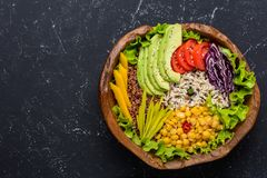 Healthy vegan food bowl with quinoa, wild rice, chickpea, tomatoes, avocado, greens, cabbage, lettuce on black stone background. Top view with copy space sport royalty free stock photo
