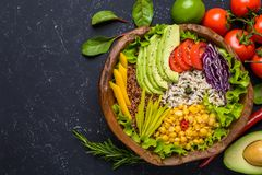 Healthy vegan food bowl with quinoa, wild rice, chickpea, tomatoes, avocado, greens, cabbage, lettuce on black stone background. Healthy vegan food bowl with royalty free stock images