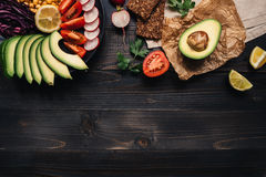 Healthy vegan food concept. Healthy food with vegetables and whole wheat bread on the wooden table top view. Copy space.  Stock Photography