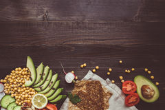 Healthy vegan food concept. Healthy food with vegetables and whole wheat bread on the wooden table top view. Copy space stock image